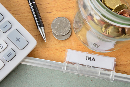 Pen, change, and calculator near IRA folder