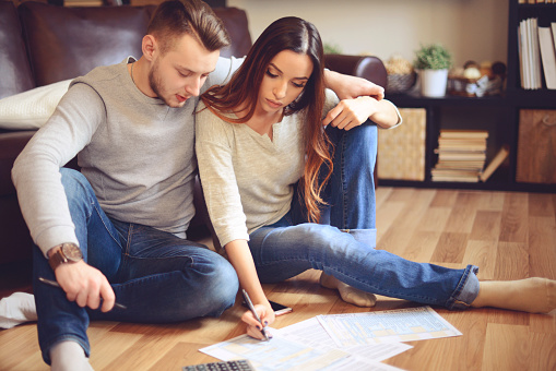 Couple sitting on floor looking at paperwork