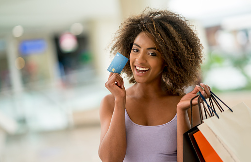 Girl holding up credit card with shopping bags