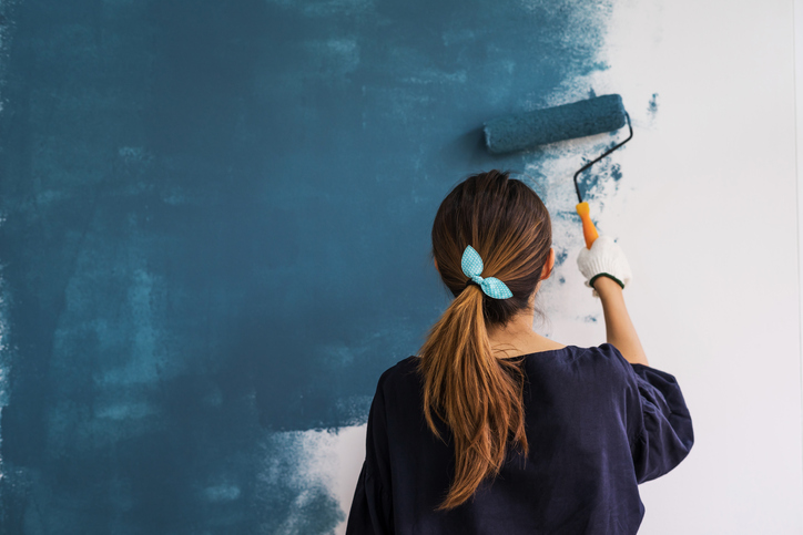 young girl painting a wall blue