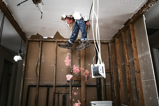 a man feet dangling through the ceiling after falling through