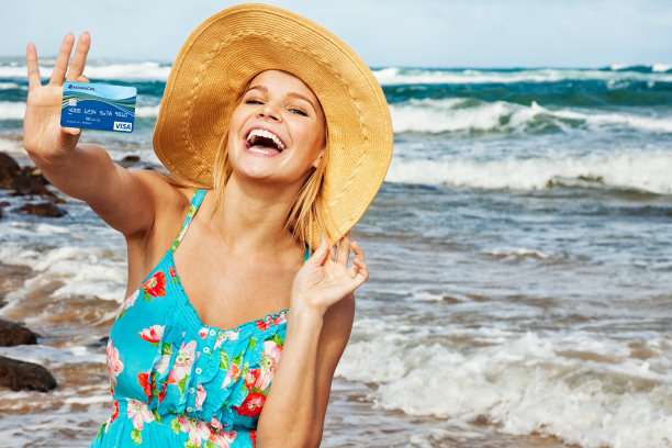 a woman on a beach holding a credit card